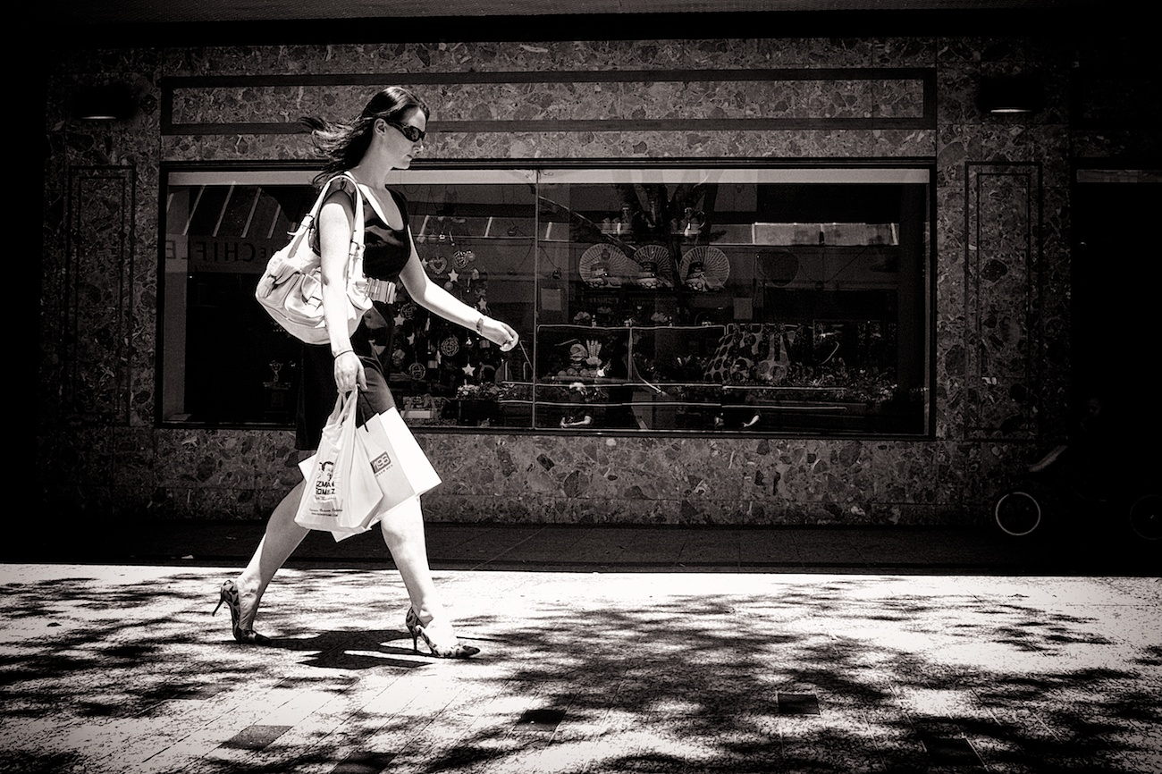Every high style shopping street in the world seems to looks the same. A cosmopolitan woman walks down Queen St. in Brisbane with Christmas displays in the background.