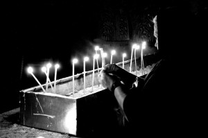 Lady lights a candle in the Church of the Holy Sepulchre (Jerusalem, Israel)