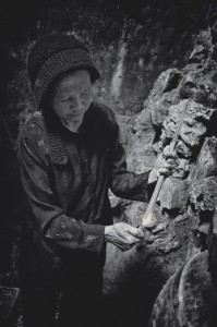 Old lady lights a handful of incense sticks in cave temple (Marble Mountain, Vietnam)