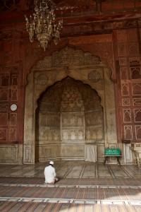 Solitary man sits praying at the Jama Masjid mosque (New Delhi, India)