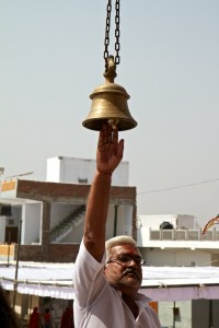 Man rings bell while walking into a Hindu temple (Outside Jaipur, India)