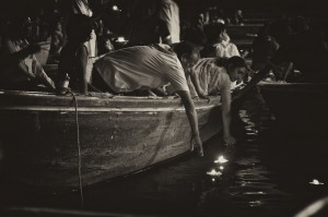 Family places floating candles on the ganges during the night ceremony (Varanasi, India)