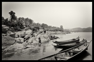 Kids panning for gold and a group of small long boats on the Mekong river in Laos