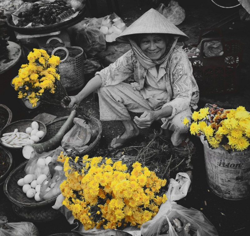A lady in the Hoi An market selling yellow flowers