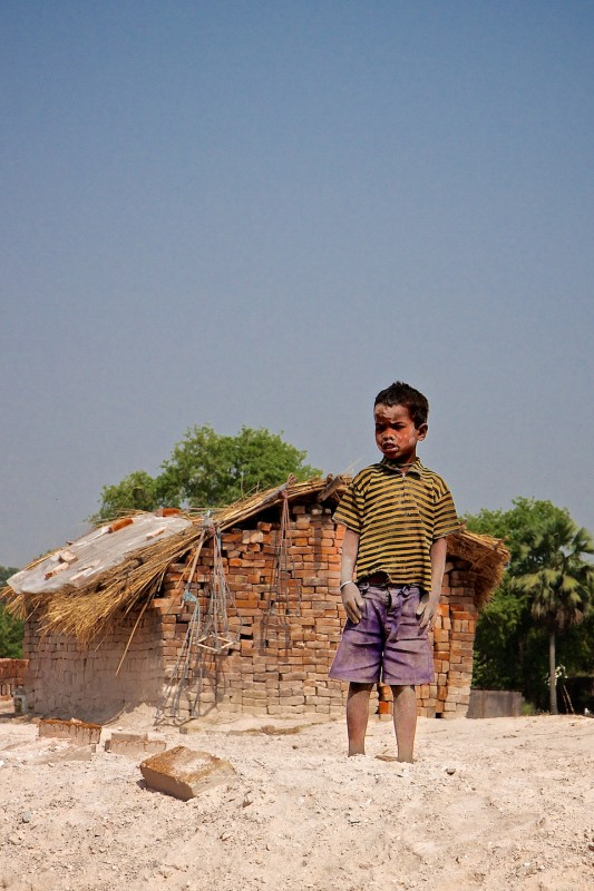 A small boy playing (possibly working) at a brick factory in Northern India