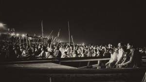 A floating congregation of pilgrims watches the night ceremony on the Ganges in Varansi, India